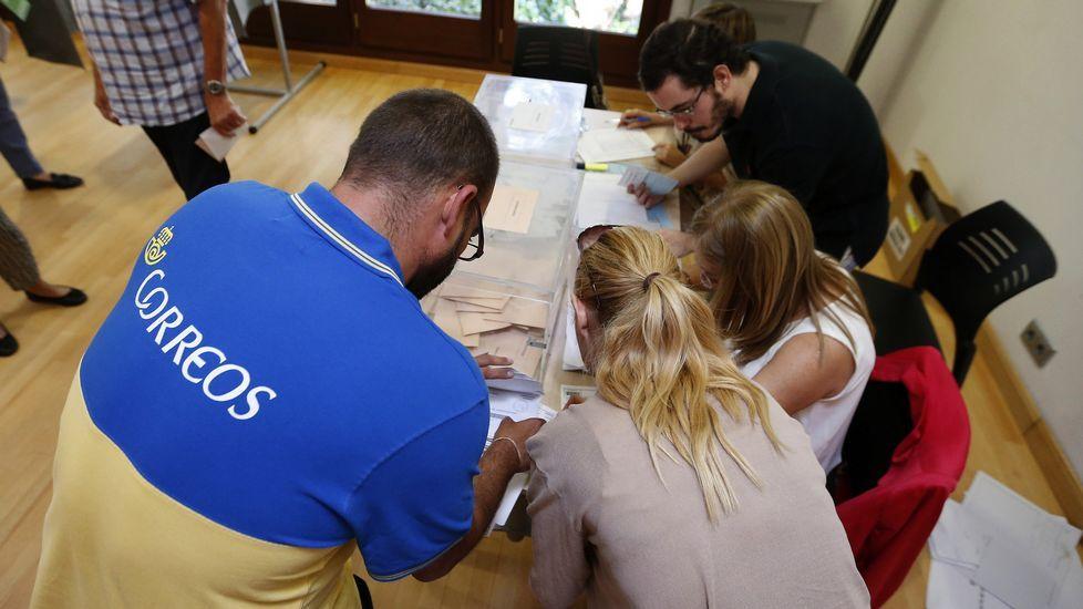 .Un funcionario de correos entrega en una de las mesas del Centro Cultural Volturno, en la localidad madrileña de Pozuelo de Alarcón, los votos por correo destinados a este colegio electoral