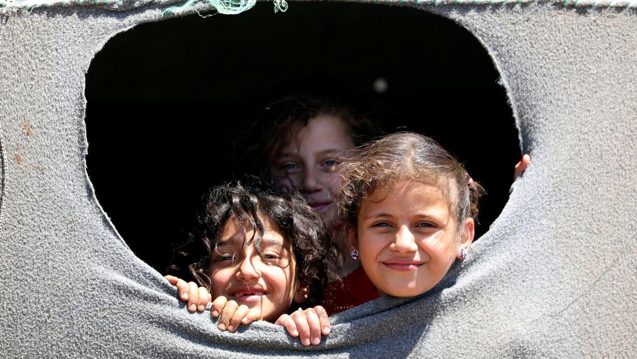 Chicas desplazadas de la provincia de Deraa miran por un agujero de una tienda cerca de los Altos del Golán, en Siria