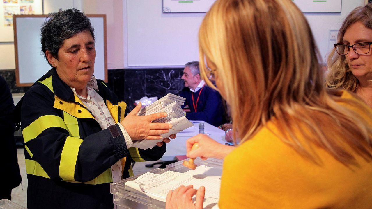 Una trabajadora de Correos entrega a la presidenta de una mesa electoral el centro Santa Clara de Portugalete (Vizcaya) votos emitidos por correo
