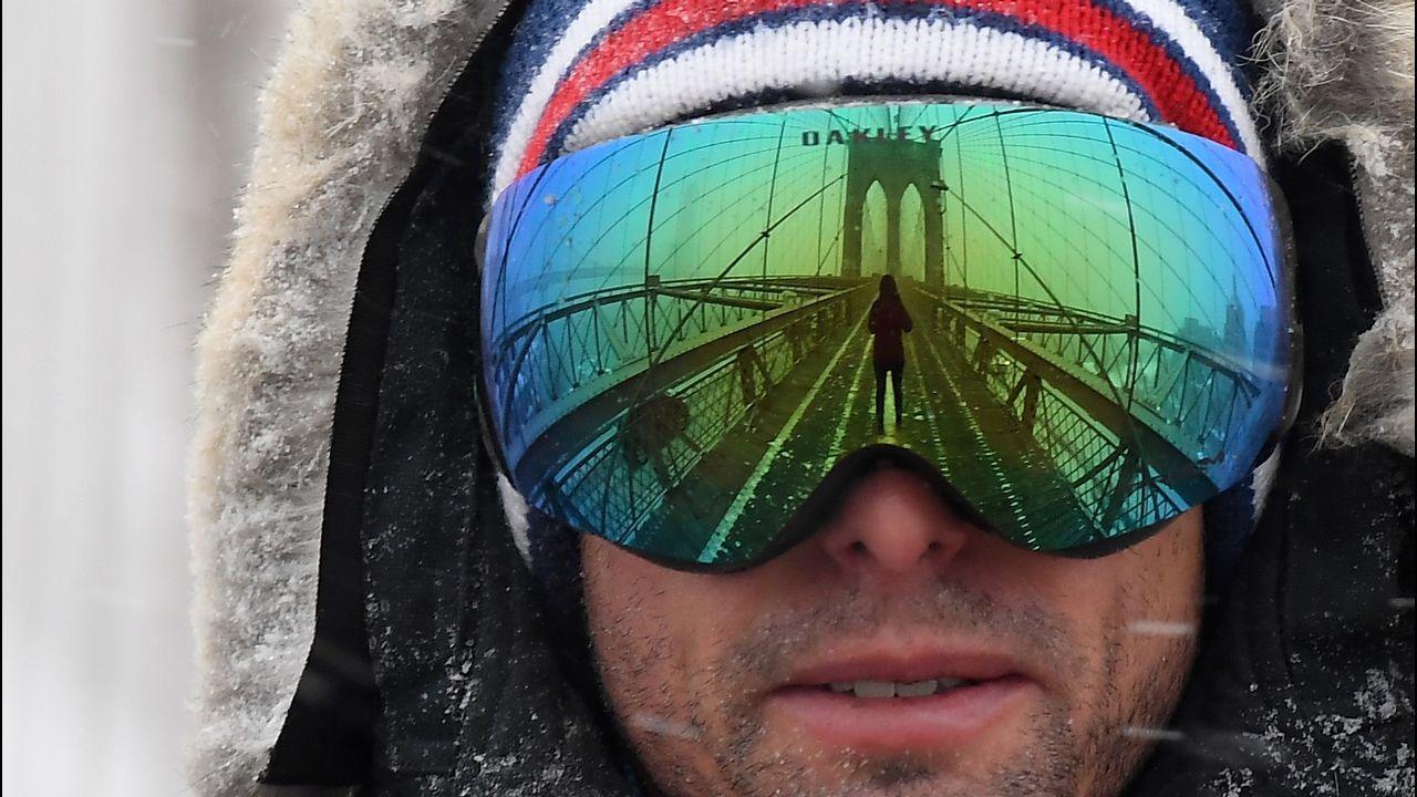 El puente de Brooklyn se refleja en las gafas de nieve de un hombre