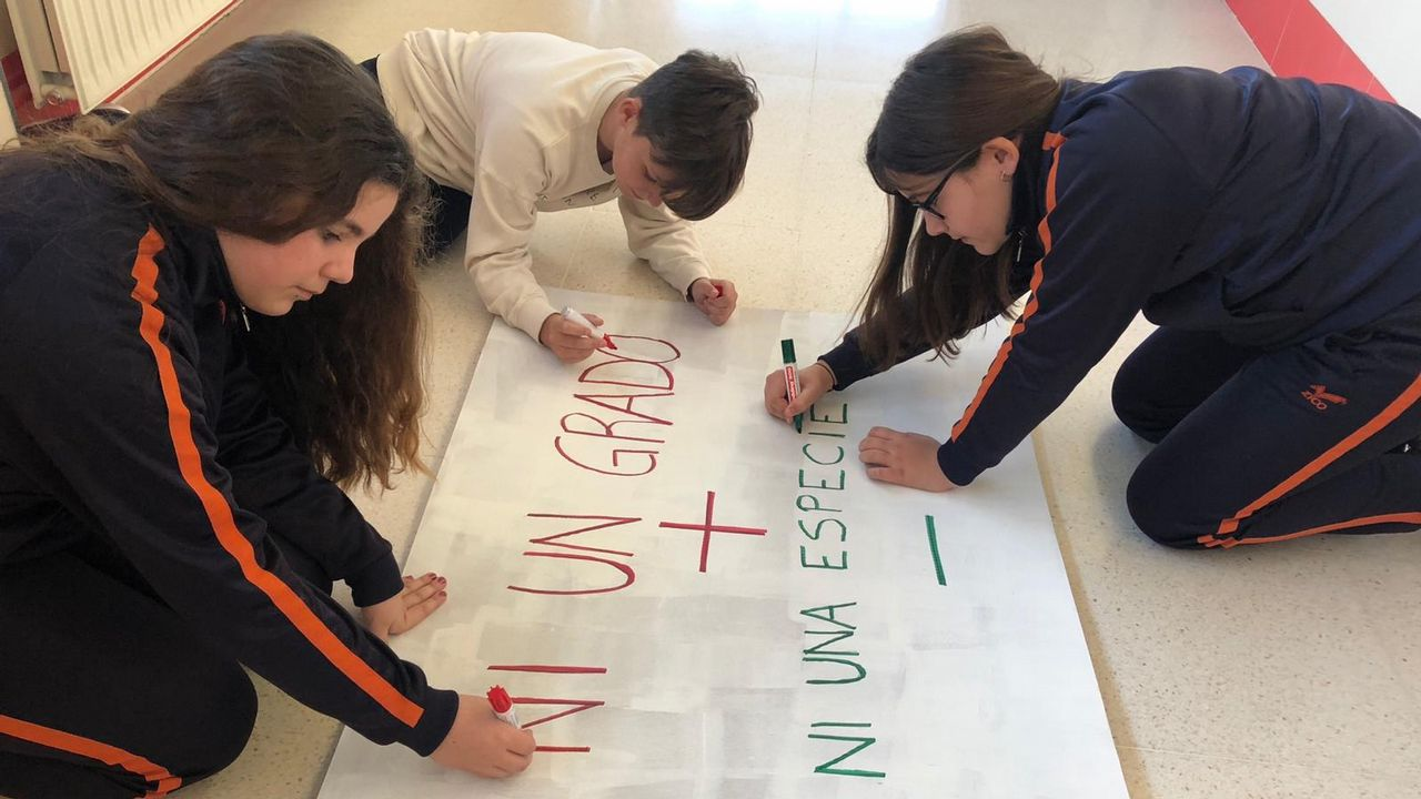 Carla, Aaron y Cintia preparan los carteles para la protesta. m. Leirós