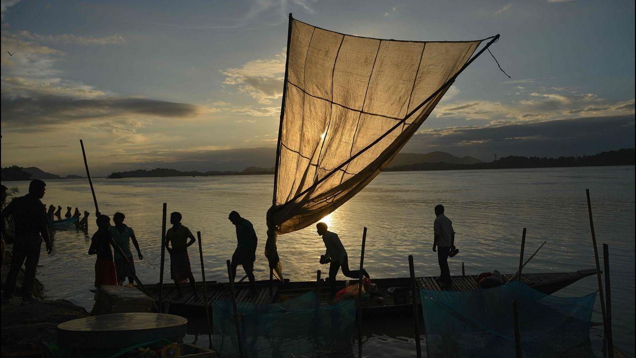 Los pescadores indios atracan su barco con pescado para vender en un mercado a orillas del río Brahmaputra en Ujanbazar Ghat en Guwahati