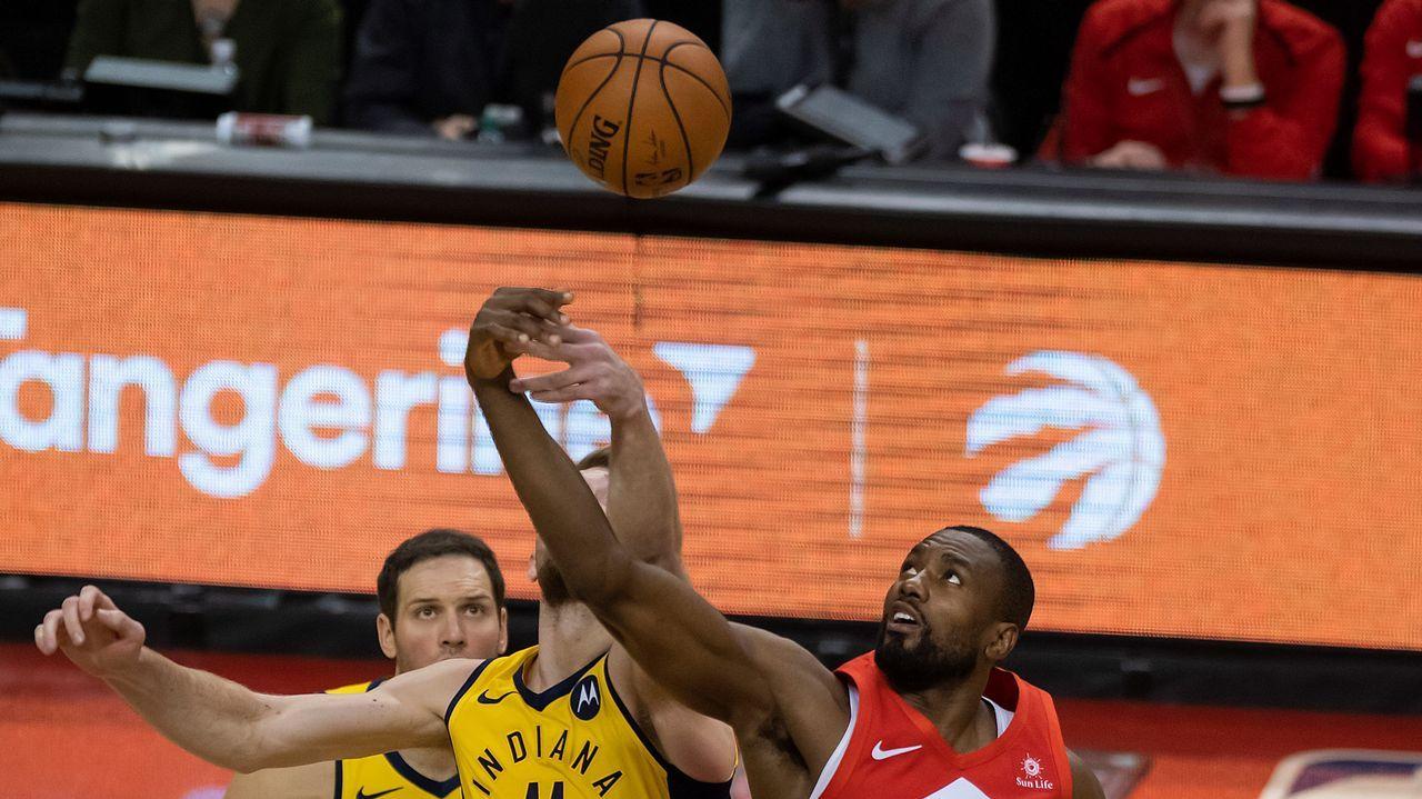 Serge Ibaka (d) de Raptors disputa el balón con Domantas Sabonis (i) de Pacers, en un partido de la NBA en Toronto