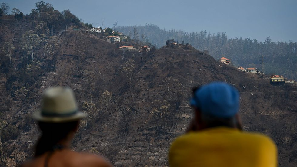 Dos personas observan la devastación causada por el fuego en un monte de Babosas, en Madeira