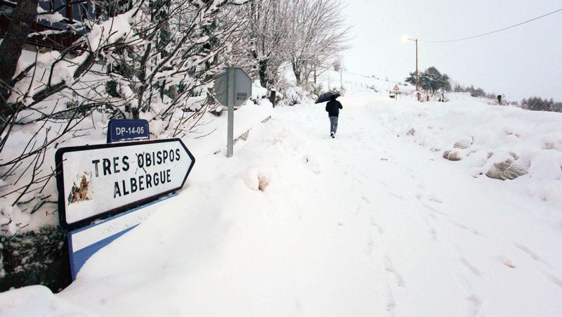 Estampas de la nevada en A Pobra do Brollón.Un visitante retratando ayer la palloza de Galán, en Pedrafita, sepultada por la nieve.