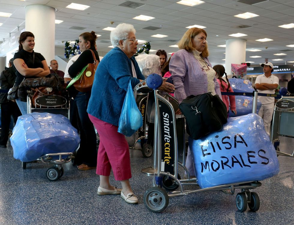 Varias personas hacen cola para embarcar en un vuelo de Miami a La Habana.