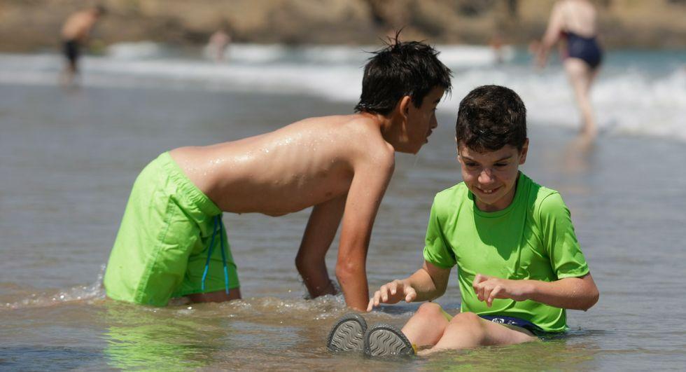 ¿Cómo ver las Perseidas?.Dos niños juegan en la orilla durante la actividad en Bastiagueiro.