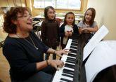 Miriam Fernández, la directora del coro, con tres de sus alumnas: Blanca, Ainara y Sara.