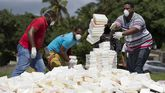 Varios operarios lanzan fardos de cocaína y heroína para ser incinerada.