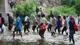 Varios inmigrantes cruzan un río de Italia en su intento de alcanzar la frontera
