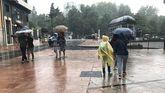 Los turistas se protegen de la lluvia en Oviedo