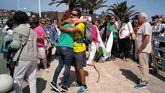 Alberto Fernández abraza a una de las personas que le esperaban en la playa Palmera de Candás, observado por su padre