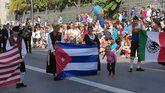 Una niña entrega un global a las jóvenes que sostienen la bandera de Cuba en el Desfile del Día de América en Asturias