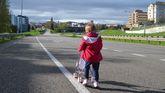 Una niña pasea a su muñeca sobre la carretera de acceso a Oviedo desde la autopista Y, cerrada al tráfico para celebrar el amagüestu del Bulevar de Santullano