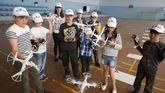 En la imagen, varios niños en un taller de drones