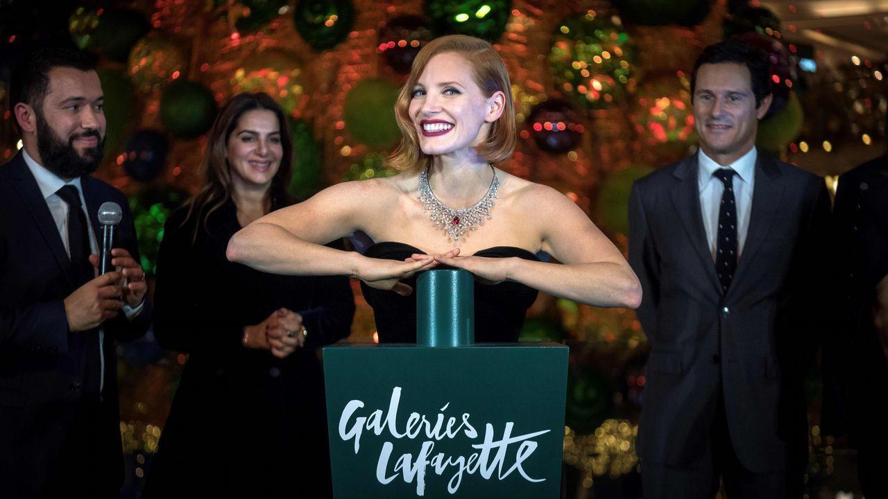 La actriz Jessica Chastain aprieta el botón que enciende las luces de Navidad en las Galeries Lafayette de París