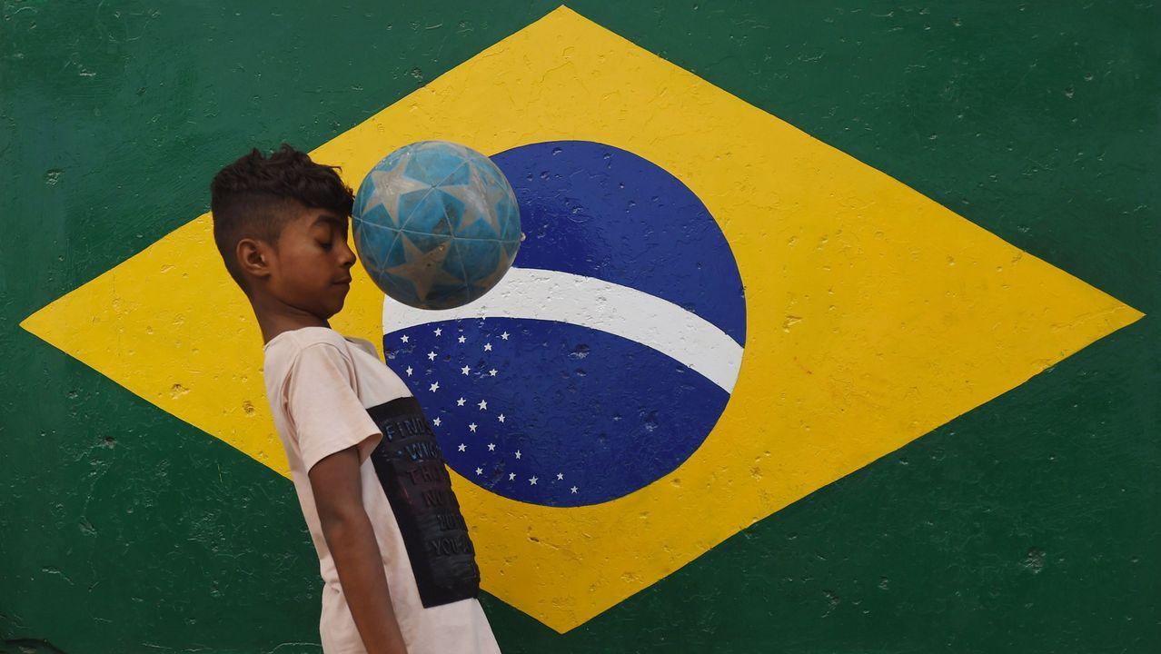 Un niño juega con una pelota frente a un mural con la bandera de Brasil