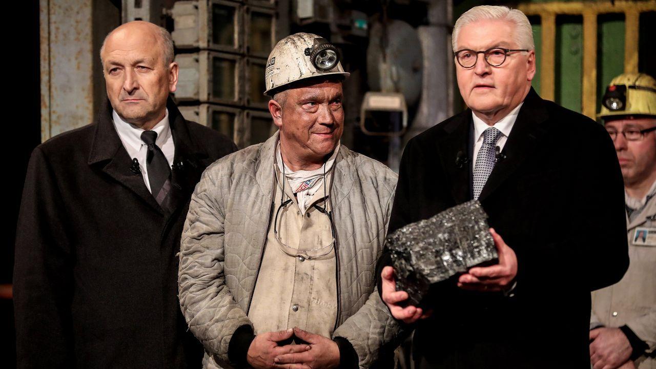 El presidente de compañía minera RAG, Peter Schrimpf (izq), y el presidente alemán, Frank-Walter Steinmeier (dcha) reciben la última roca de carbón extraída de manos del minero Jürgen Jakubeit (c) durante la ceremonia de cierre de la mina de carbón Prosper-Haniel en Bottrop (Alemania) hoy, 21 de diciembre de 2018. Alemania selló hoy una página de su historia industrial con el cierre del pozo minero, el último que seguía funcionando en la cuenca del Ruhr (oeste), una región que durante siglos explotó su llamado  oro negro , el carbón