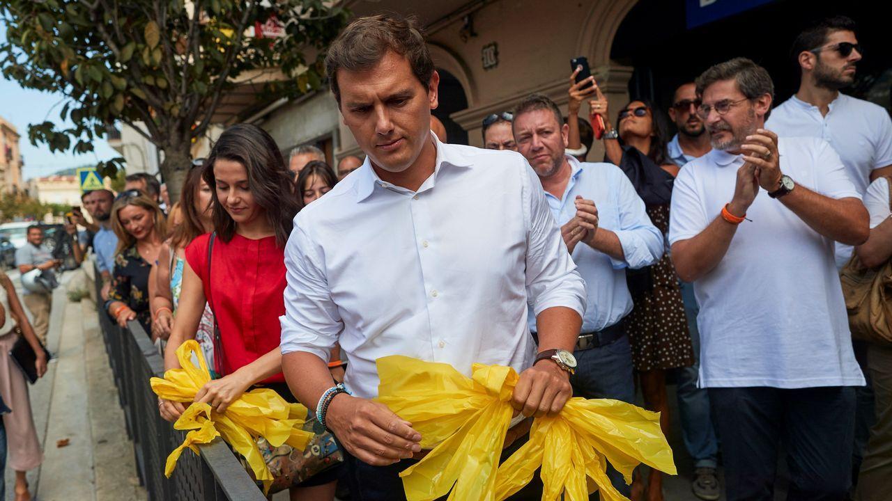 .El presidente de Cs y su líder en Cataluña, Albert Rivera e Inés Arrimadas, retiran lazos amarillos durante el recorrido que hicieron junto a cargos y afiliados del partido por la localidad barcelonesa de Alella