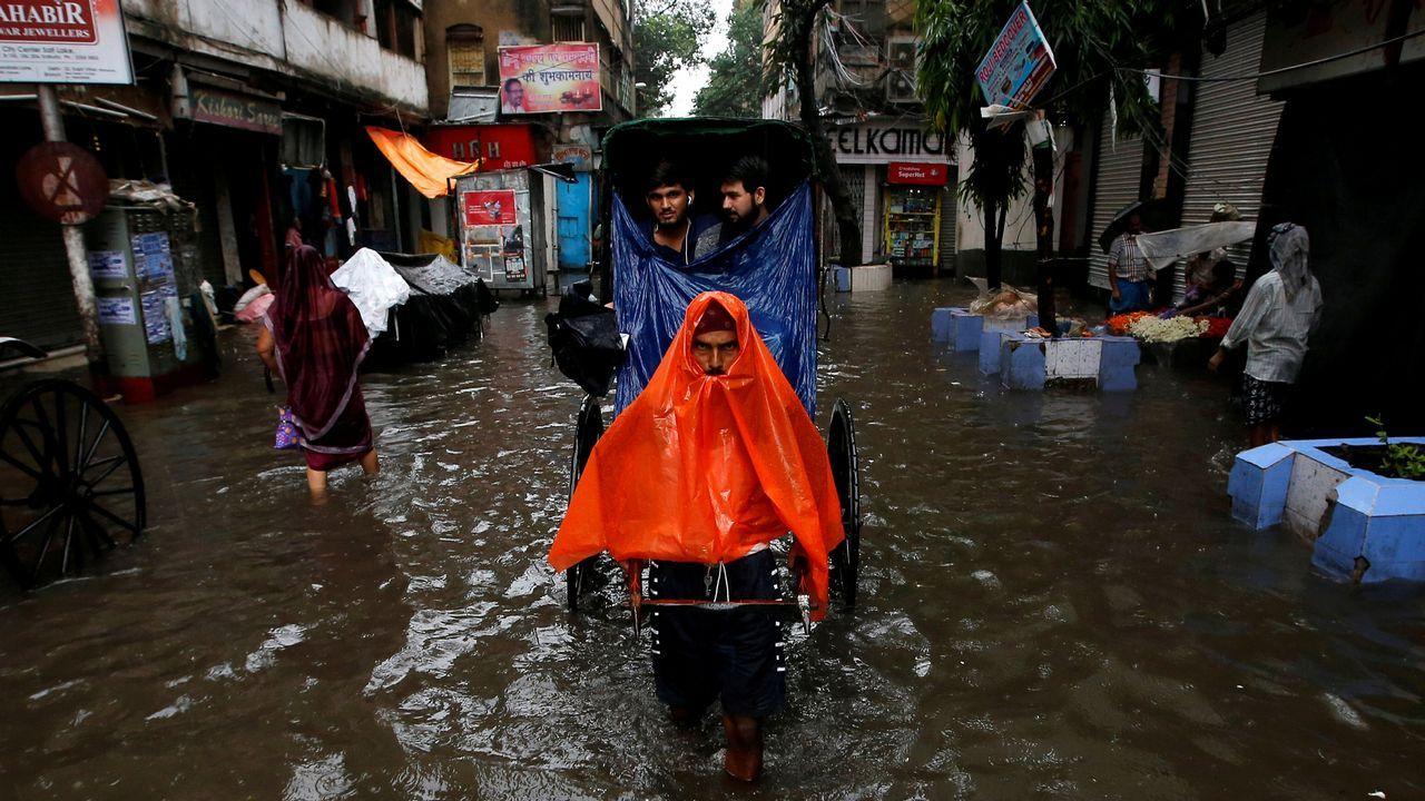 .Un hombre tira de un carruaje en las calles inundadas de Calcuta