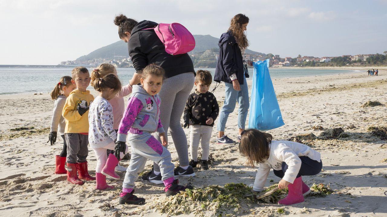Mañana de limpieza de arenales en la Costa da Morte: ¡el álbum!.Una joven pareja paseando con su bebé por un parque de Vigo