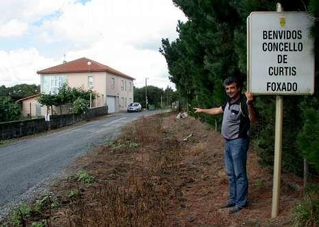 .López con la señal de linde mal colocada y el camino sin asfaltar detrás, así como su casa .