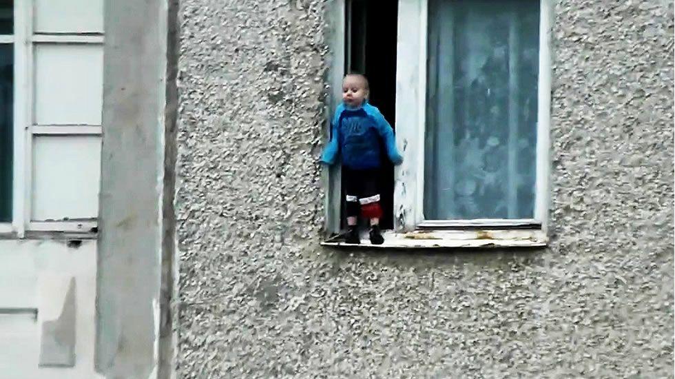 Jugando en el alféizar de una ventana abierta.