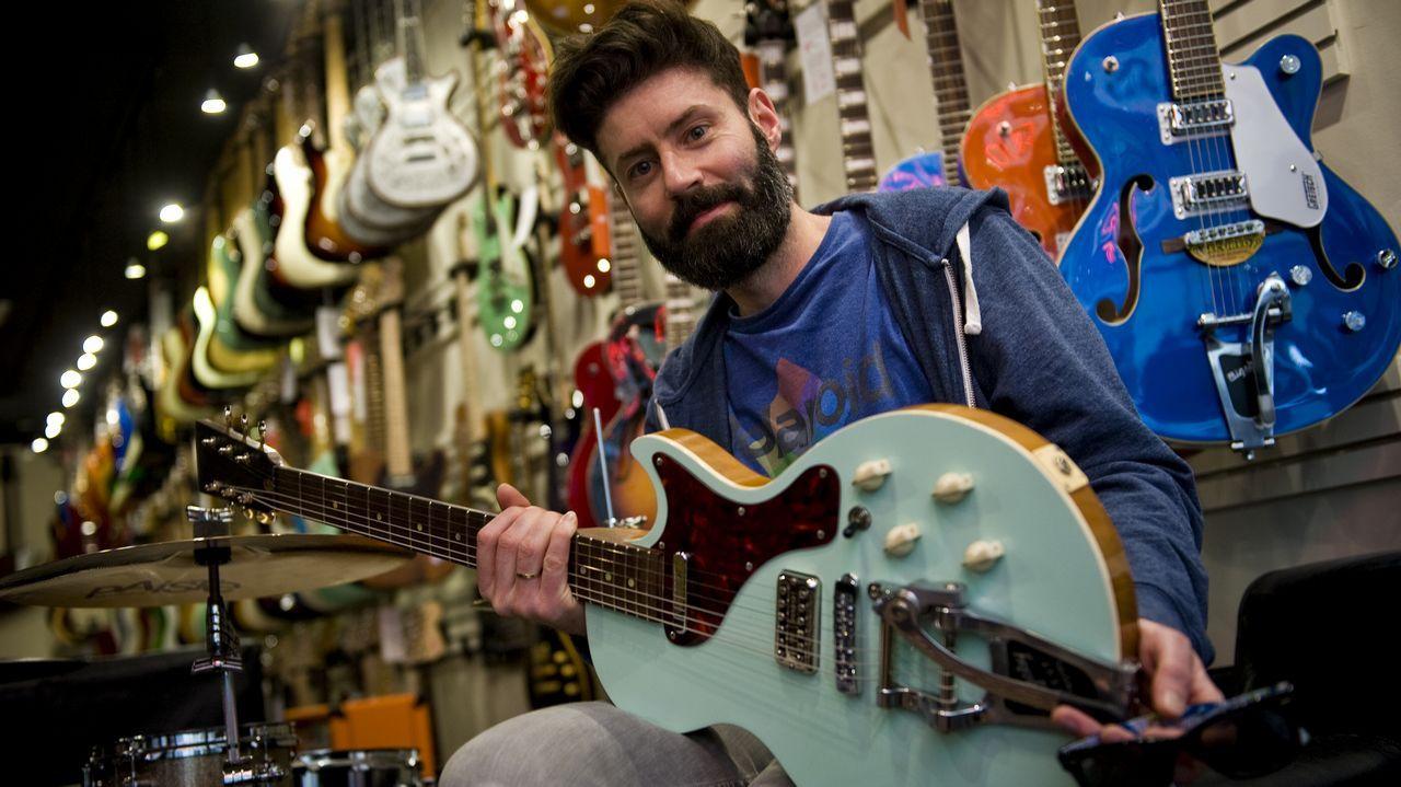 Fran Borrego, dueño de la tienda Rockbox de A Coruña, con decenas de guitarras eléctricas a sus espaldas