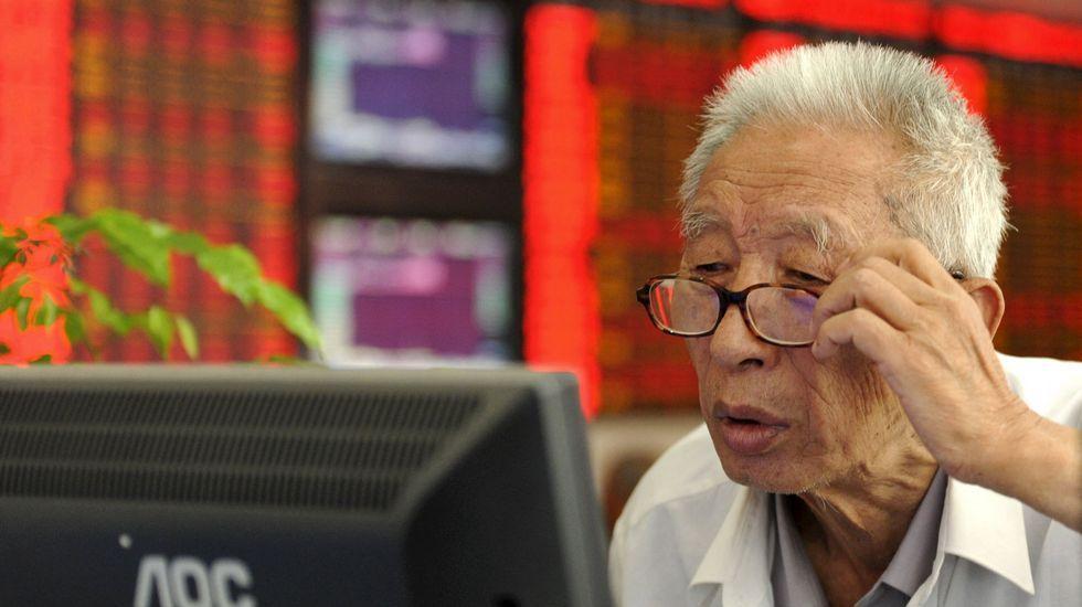 Un inversor chino observa preocupado la pantalla de precios.