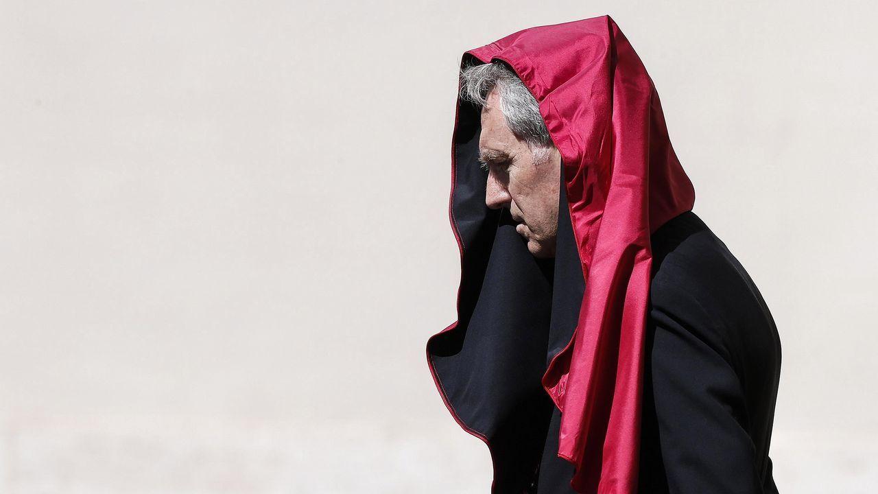 .Una ráfaga de viento coloca la toga del arzobispo Georg Gaenswein sobre su cabeza mientras espera la llegada del presidente francés, Emmanuel Macron