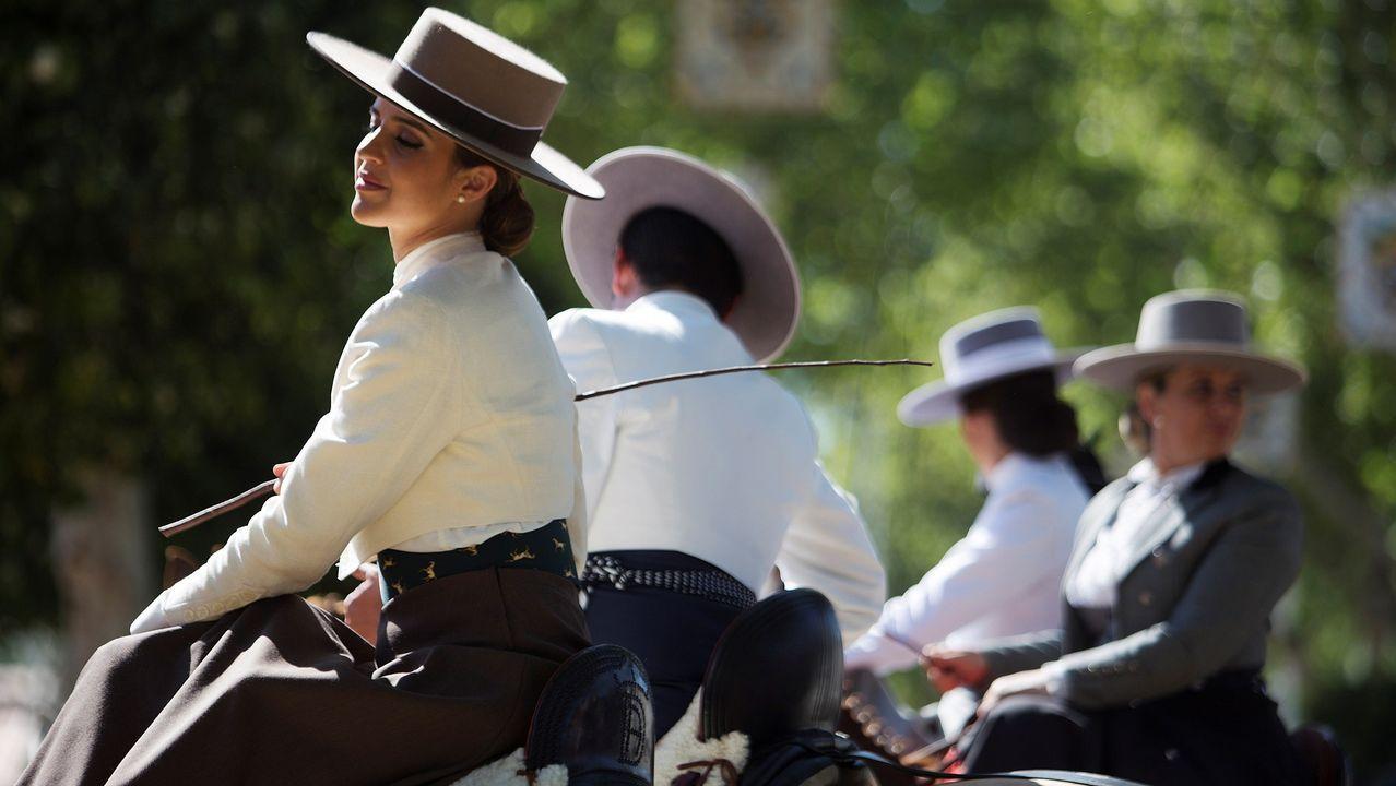 .Un grupo de personas pasean a caballo en el recinto ferial de Sevilla