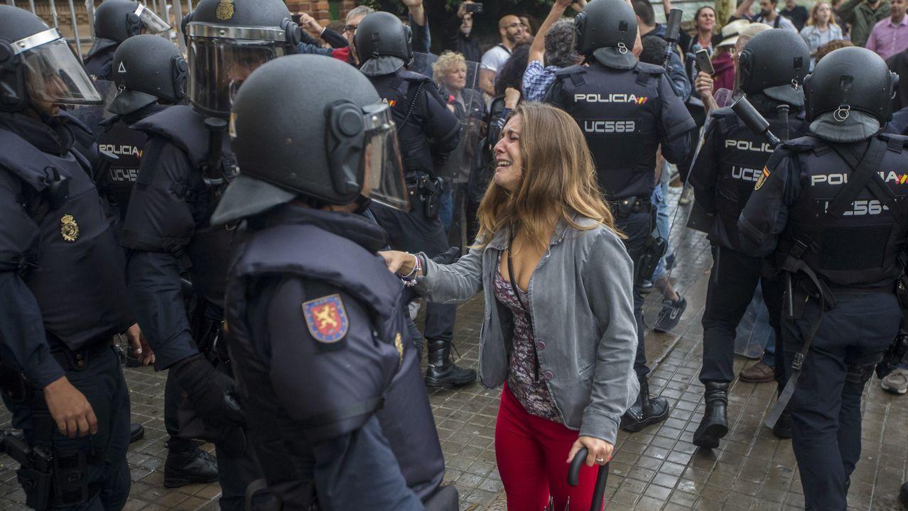 Una mujer se dirige a un agente de la Policia Nacional en los exteriores de un colegio electoral.