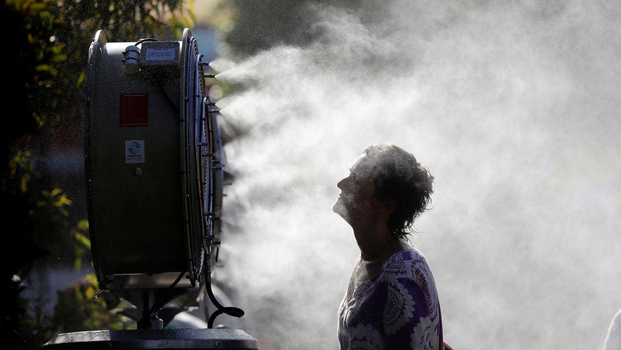 - Una mujer se refresca delante de un ventilador brumizador durante el primer día del Abierto de Australia que se disputa en Melbourne