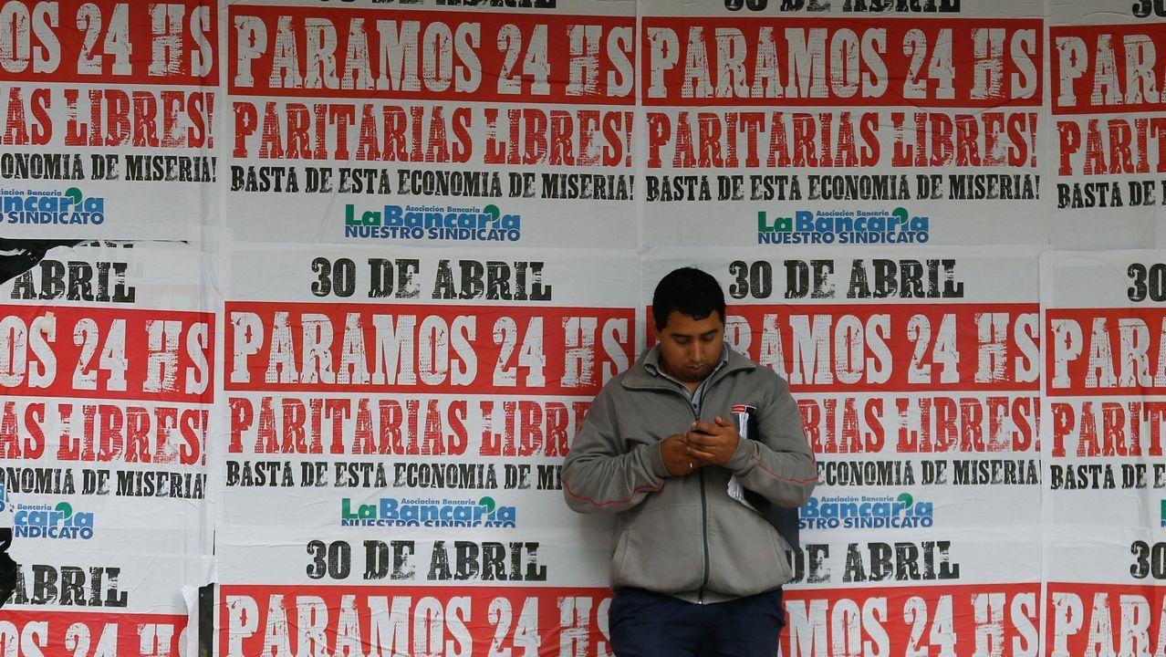 Comisiones y UGT salen en Vigo a la calle contra la reforma laboral. Un hombre mira un teléfono en un muro con carteles que llaman a la huelga general