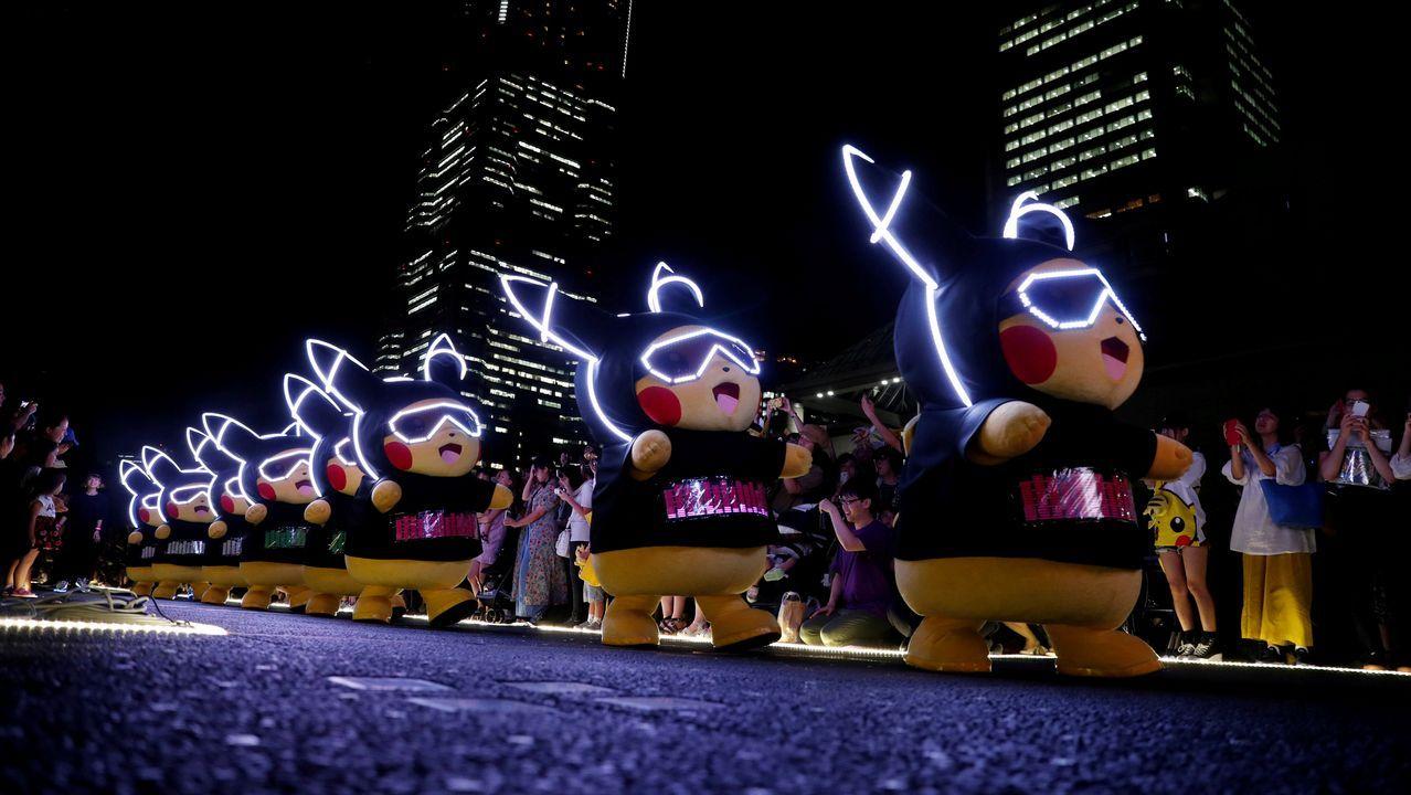 Artistas que interpretan a personajes de Pokémon con los trajes de Pikachu participando en un desfile nocturno en Yokohama, Japón