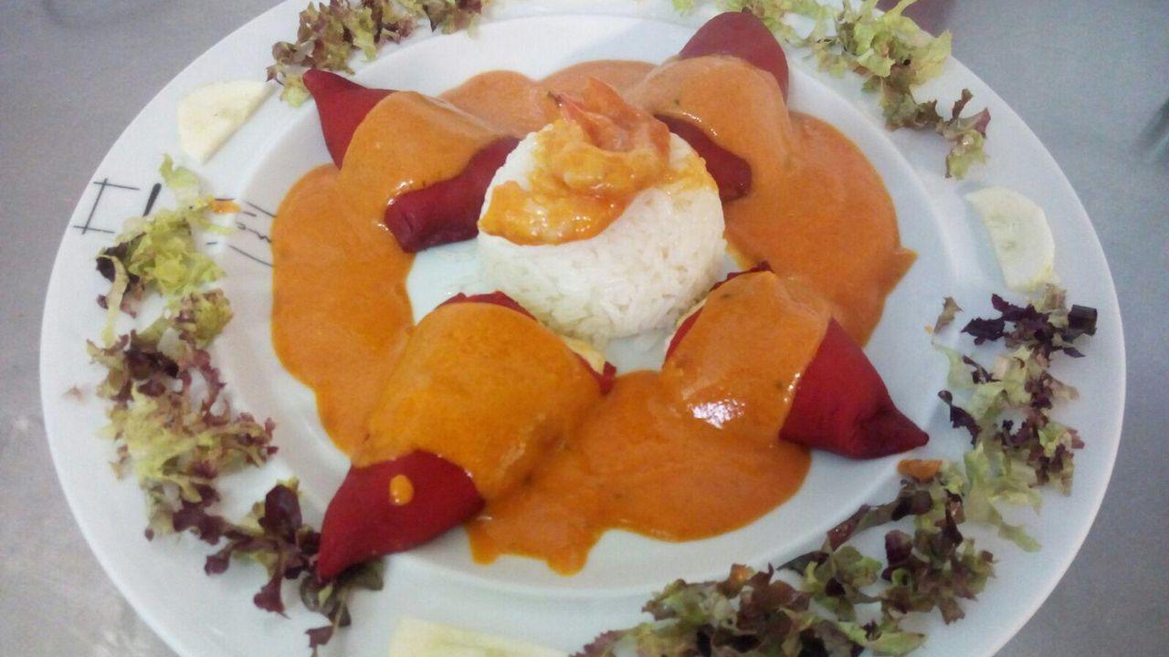 Entrante. Una ración abundante de pimientos del piquillo rellenos de bacalao y salsa de «cherrys»