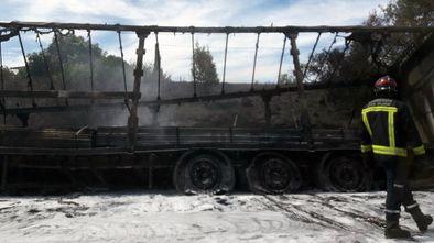 Un bombero pasa delante del camión calcinado, en el arcen de la autopista Y