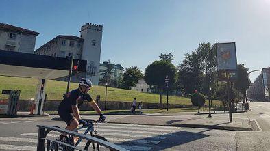 Un ciclista pasa por delante de un termómetro que marca 36 grados, en el centro de Oviedo