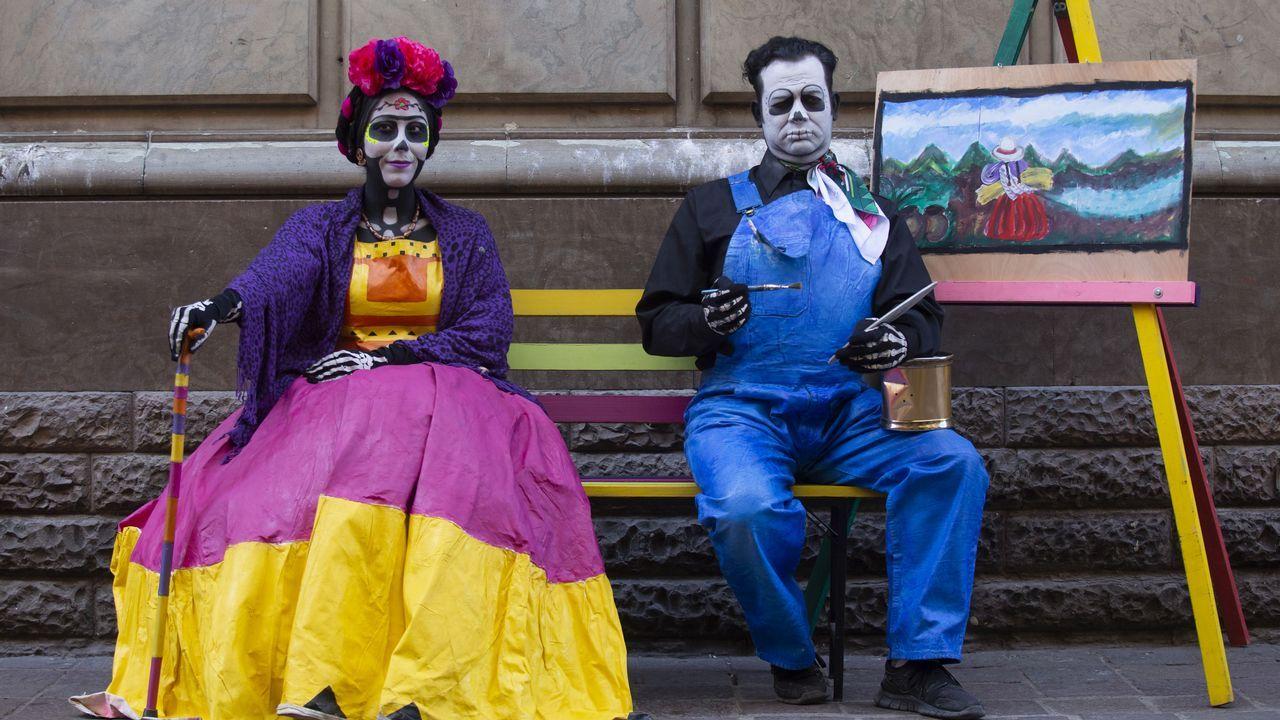 Personas caracterizados de los pintores mexicanos Frida Kahlo y Diego Rivera posan en una calles del centro histórico de la ciudad de Guanajuato (México)
