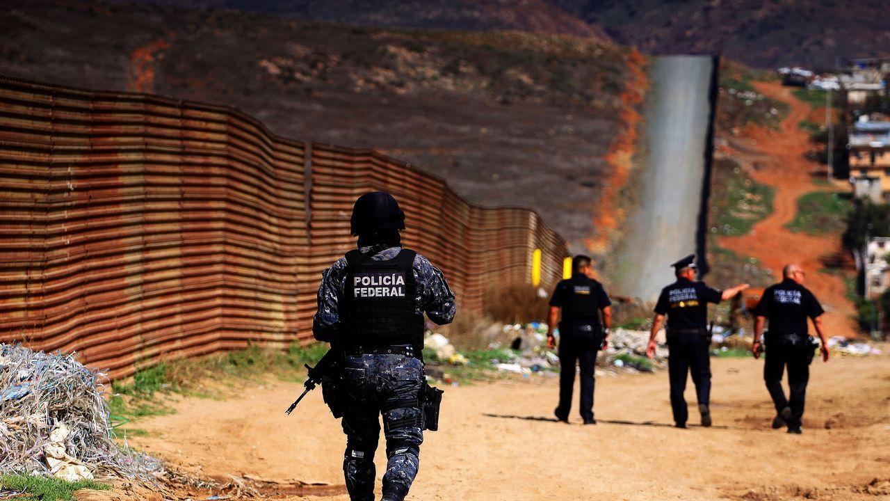 Policías federales custodian la valla fronteriza que delimita México con Estados Unidos en el estado de Tijuana