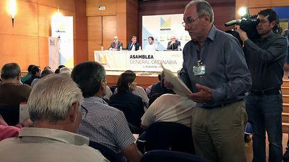 Alberto Rubio consulta documentación antes de iniciar la asamblea del Montepío de la Minería, con Juan José González Pulgar y el resto de la dirección al fondo