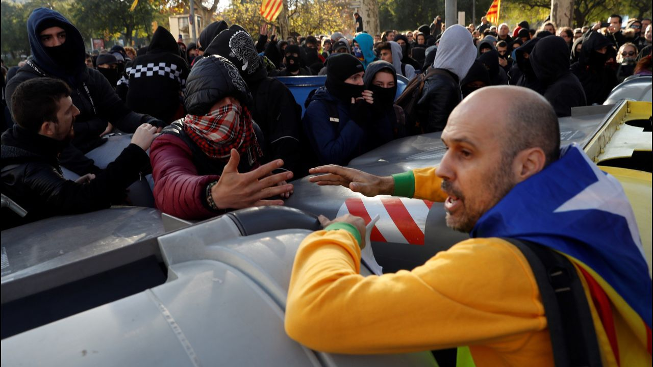 Un manifestante independentista trata de impedir que un grupo de encapuchados vuelquen contenedores en las inmediaciones de la Llotja de Mar de Barcelona