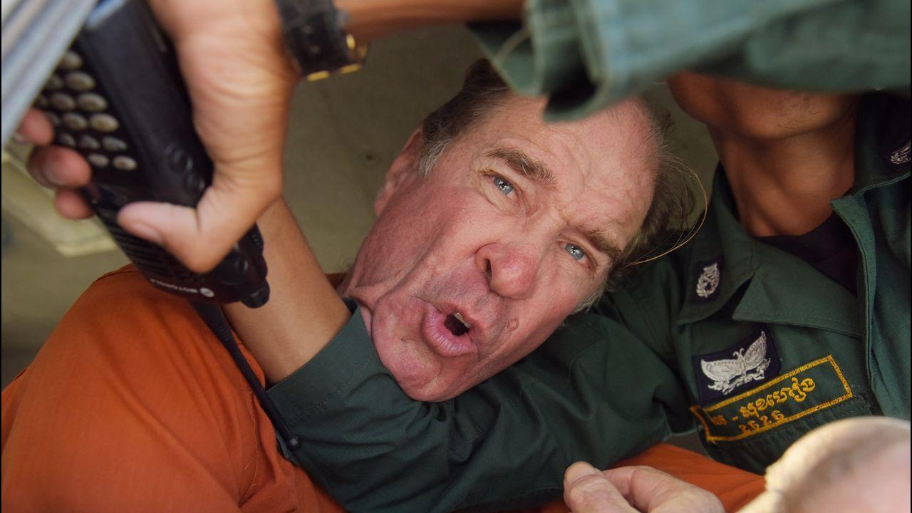 .El cineasta australiano James Ricketson es bloqueado por un policía camboyano al interior de una camioneta durante su traslado desde el Tribunal municipal en Phnom Penh