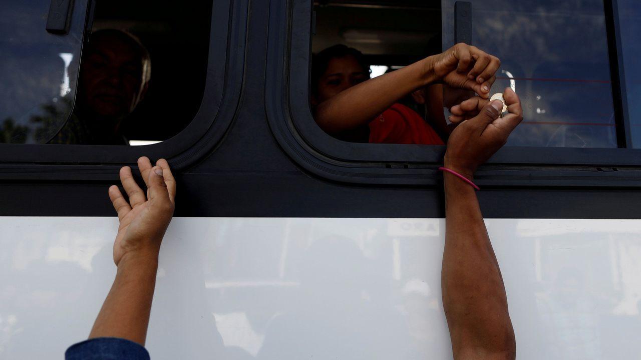 .Un grupo de migrantes centroamericanos piden dinero a los viajeros de un microbús para desplazarse a la oficina del Instituto Nacional de Migración de México