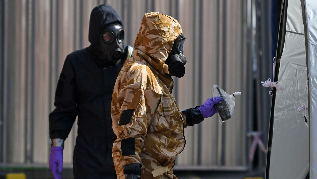.Dsos hombres, con un trajes de protección, guantes y  máscaras de gas trabajan investigando la intoxicación de un hombre y una mujer en circustancias similares a las del exespía ruso
