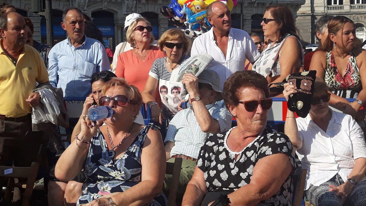 Asistentes al desfile del Día de América se protegen del sol y las altas temperaturas