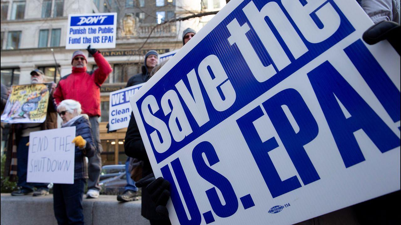 Varias personas protestan contra el cierre del gobierno en el exterior de una oficina de correos en Boston