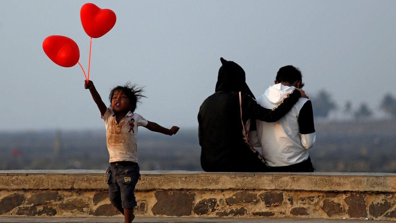 Un niño juega con dos globos con motivos de San Valentín en India mientras una pareja disfruta de la jornada justo detrás del pequeño.