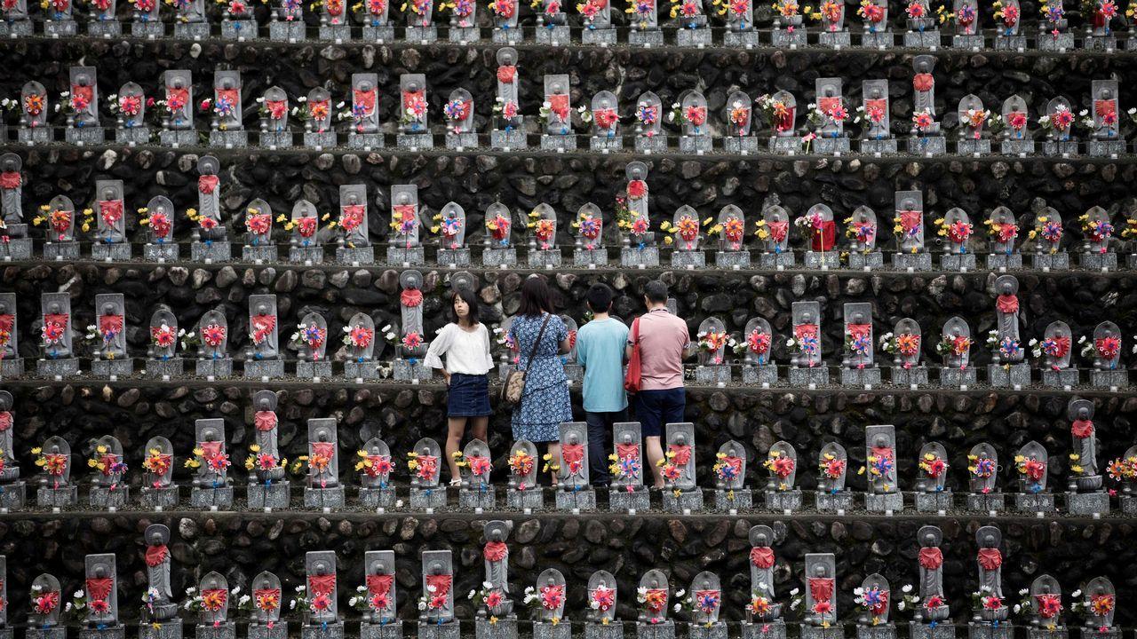 Una familia rinde homenaje frente a las estatuas jizo en el templo budista Jizoji en Oganomachi, prefectura de Saitama, para las almas de los niños por nacer y los que murieron a una edad temprana, durante el período de oración Obon.