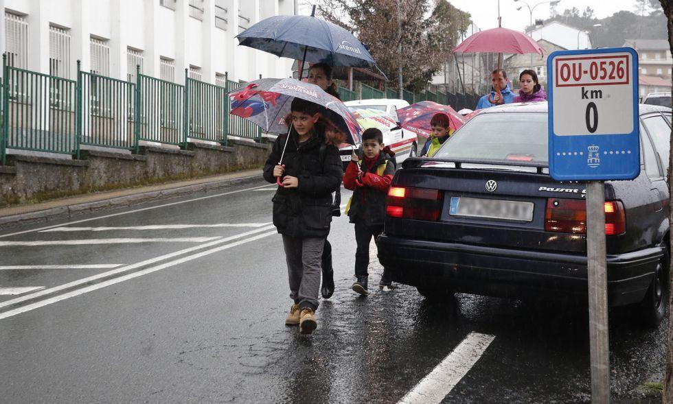 <span lang= es-es >Por el medio de la carretera</span>. La ausencia de acera en uno de los dos márgenes de la carretera de Vilar obliga a los escolares a transitar por el medio de la calzada, con el riesgo que eso conlleva.